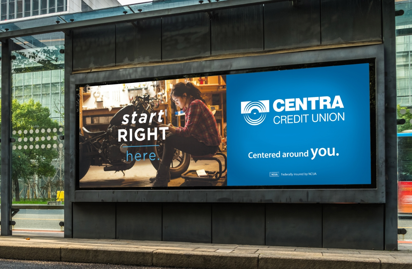 Centra Credit Union outdoor ad on bus stop featuring woman and motorcycle.