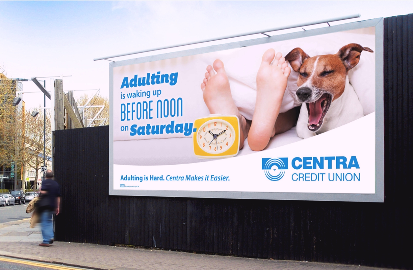 Centra Credit Union billboard above sidewalk featuring dog and clock.