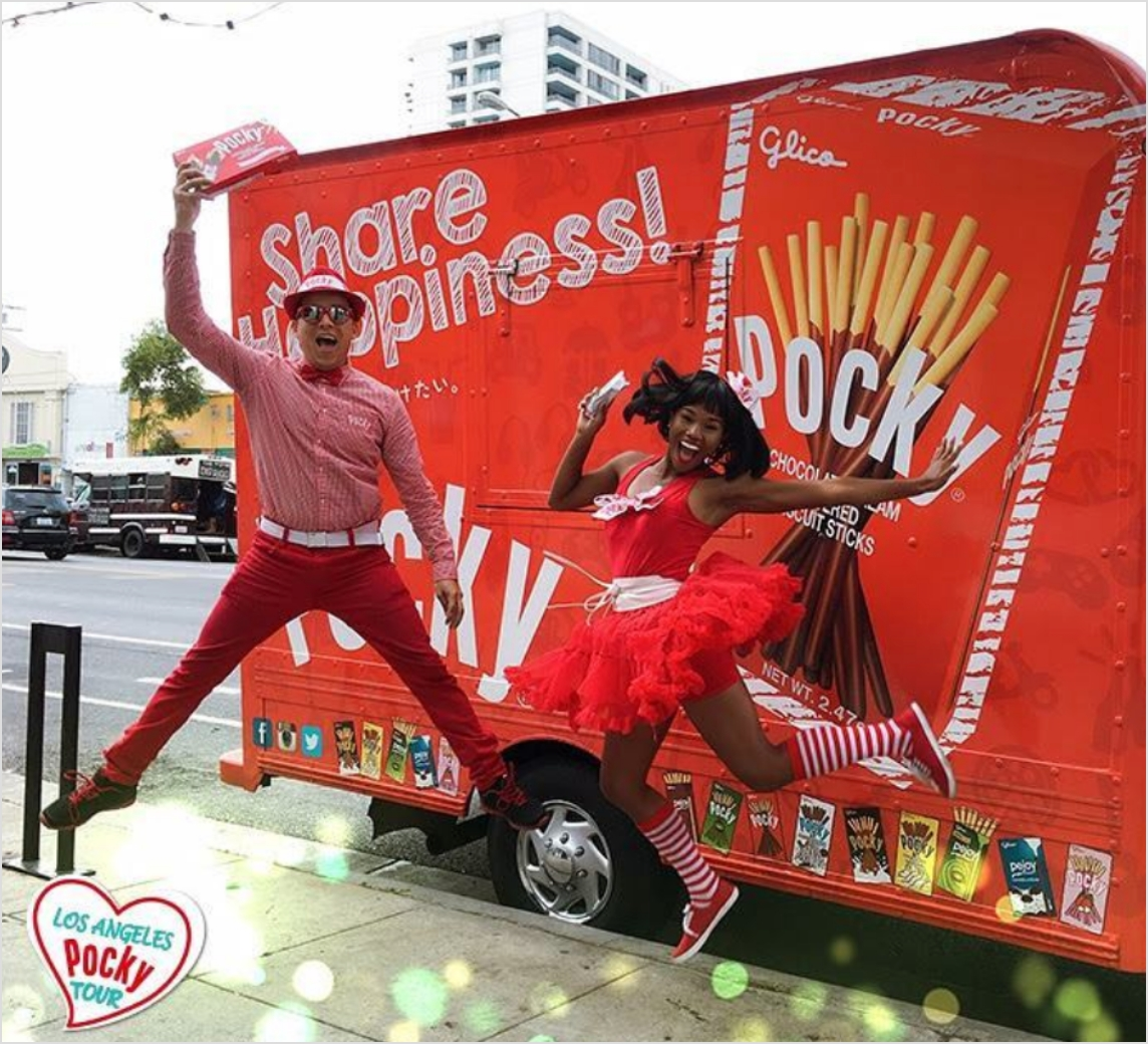 Pocky brand ambassadors on sidewalk with truck.