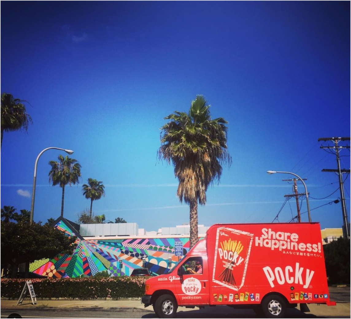 Pocky truck at curb with palm tree.